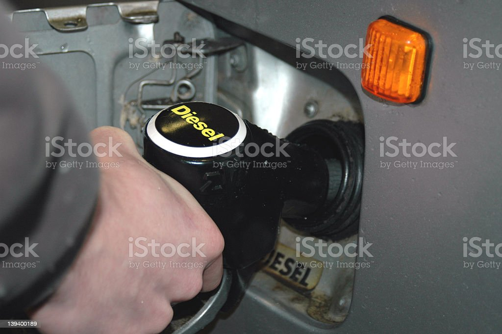 Closeup of hand pumping diesel fuel into vehicle  stock photo