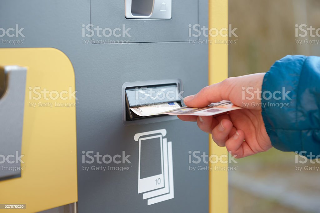 Closeup of hand putting money into automatic payment machine stock photo