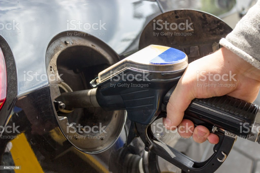 Close-up of hand refueling car's tank by holding petrol pump nozzle stock photo