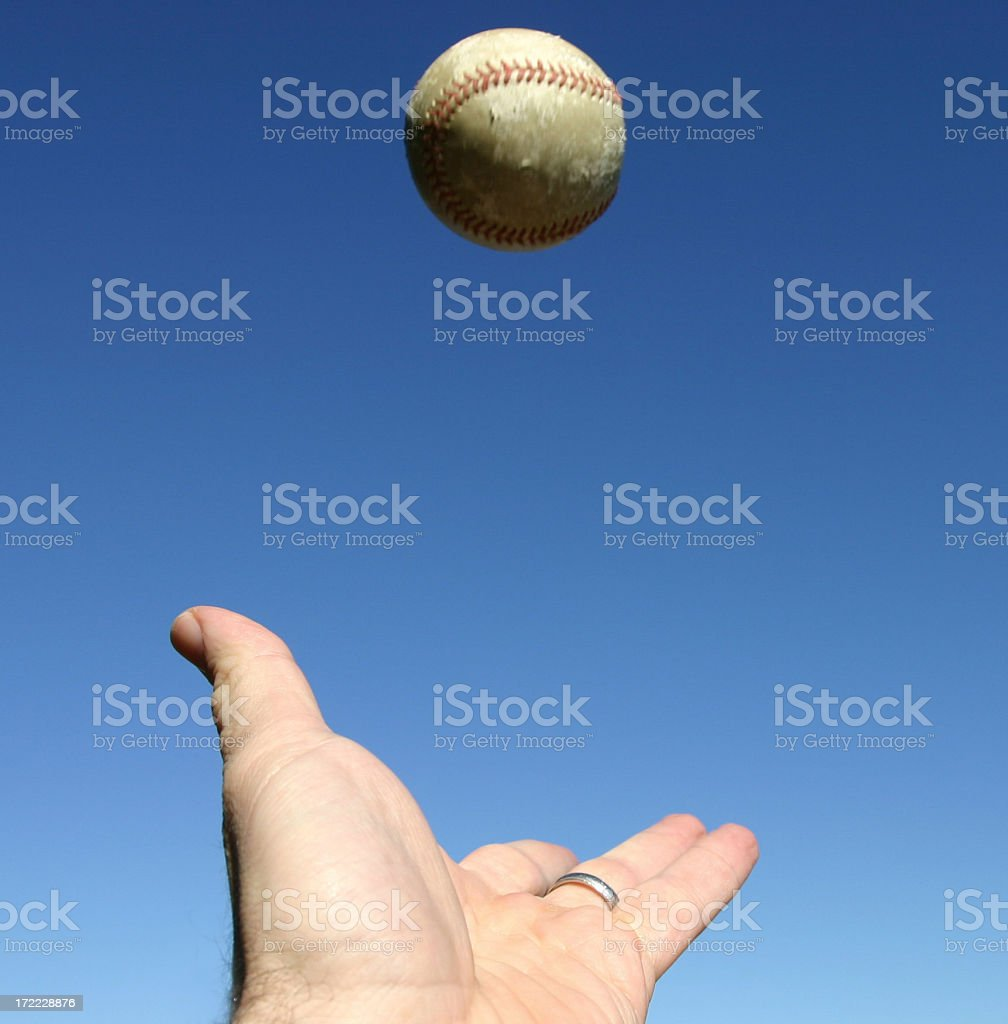 Close-up of hand trying to catch a ball in the sky stock photo