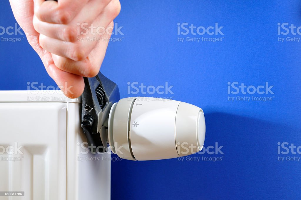 Close-up of hand turning off thermostat on white radiator, wrench stock photo
