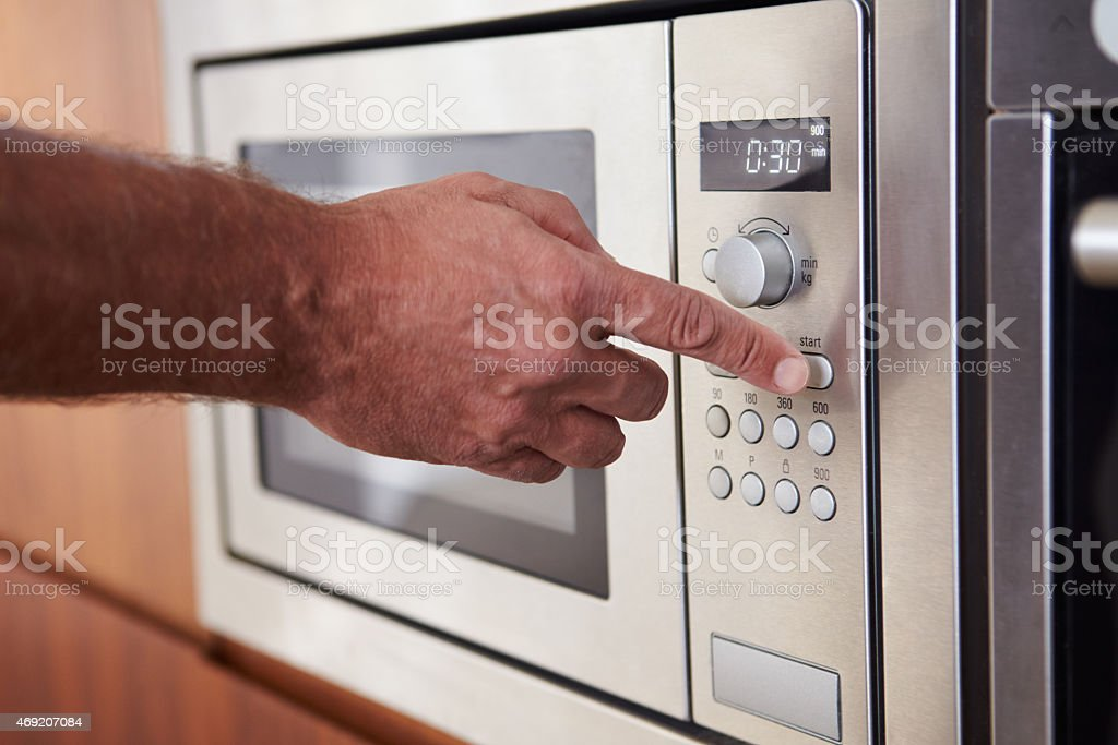 Close-up of hand using microwave stock photo