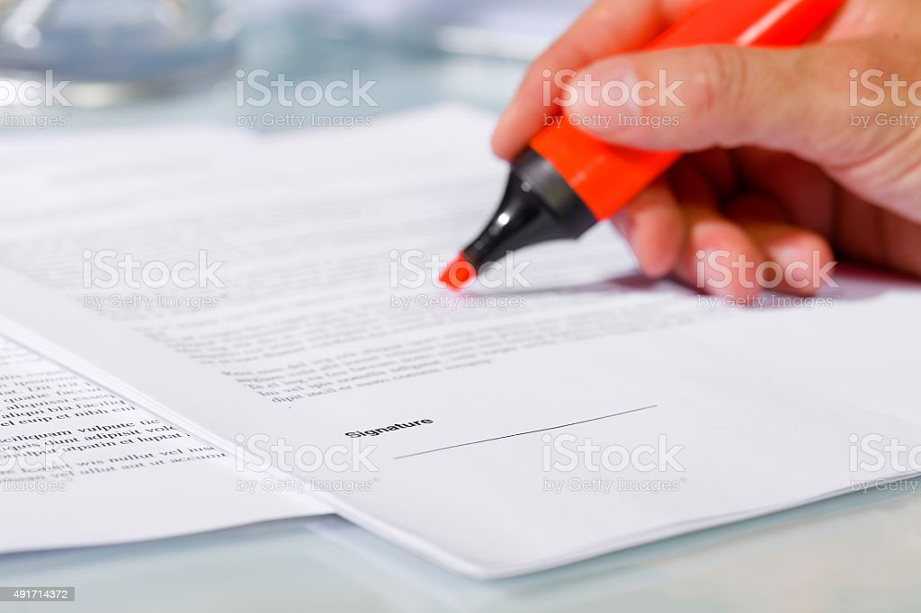 Close-up of hand with highlighter over document stock photo