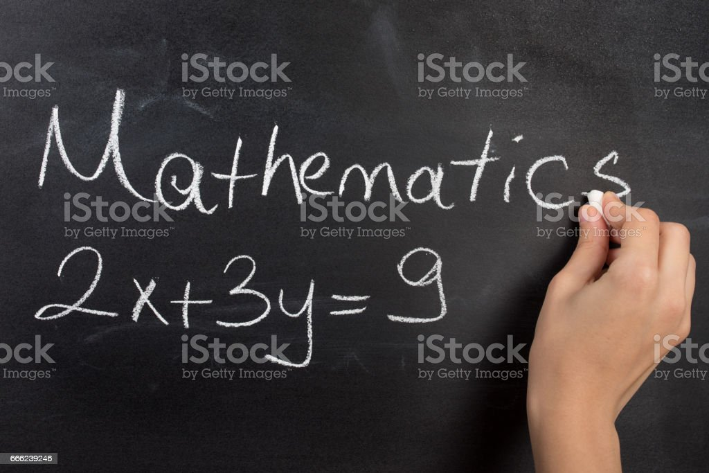 Closeup of hand writing complicated math equation on black board. stock photo
