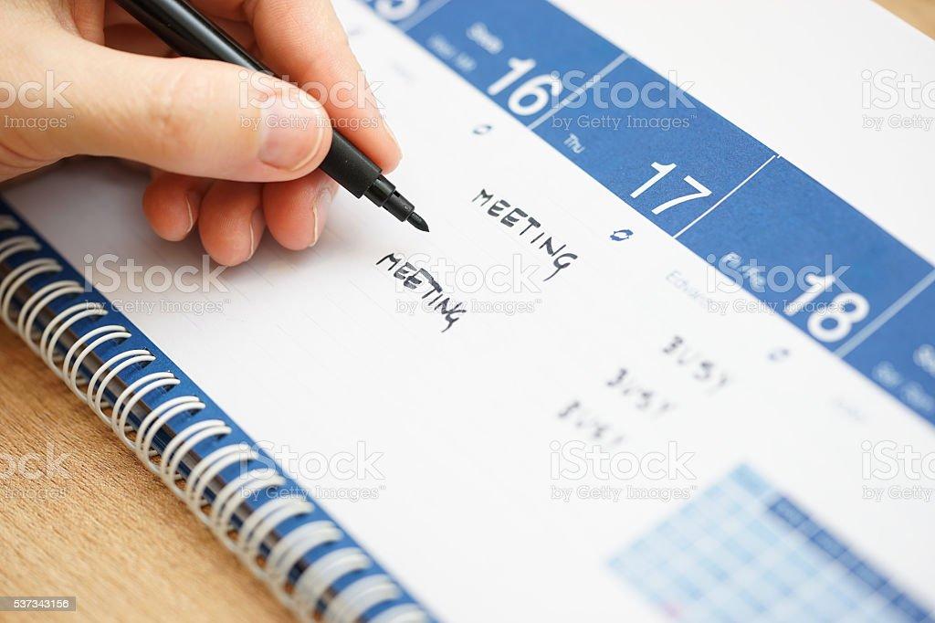 closeup of hand writing events on calendar stock photo