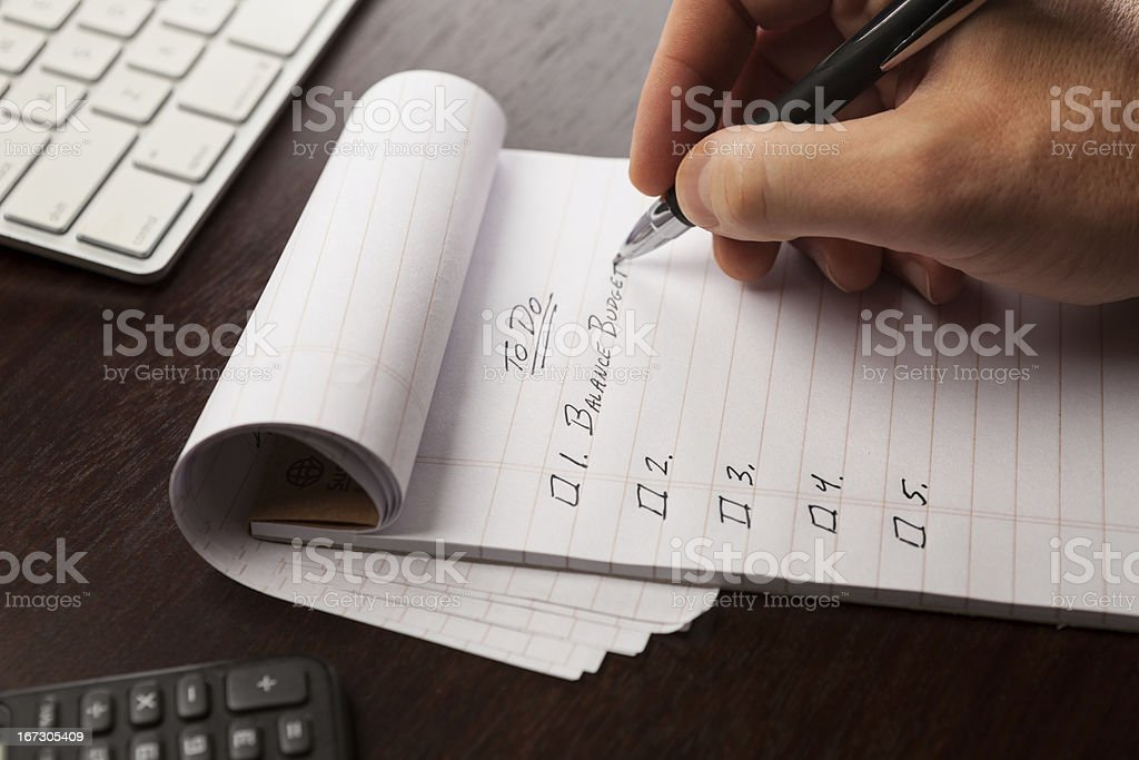 Closeup of Hand Writing in Notepad Making To Do List stock photo
