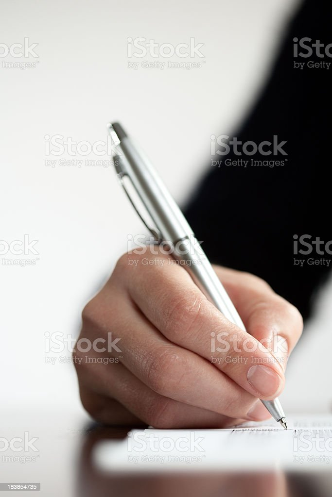 Close-up of hand writing with a silver ballpoint pen stock photo