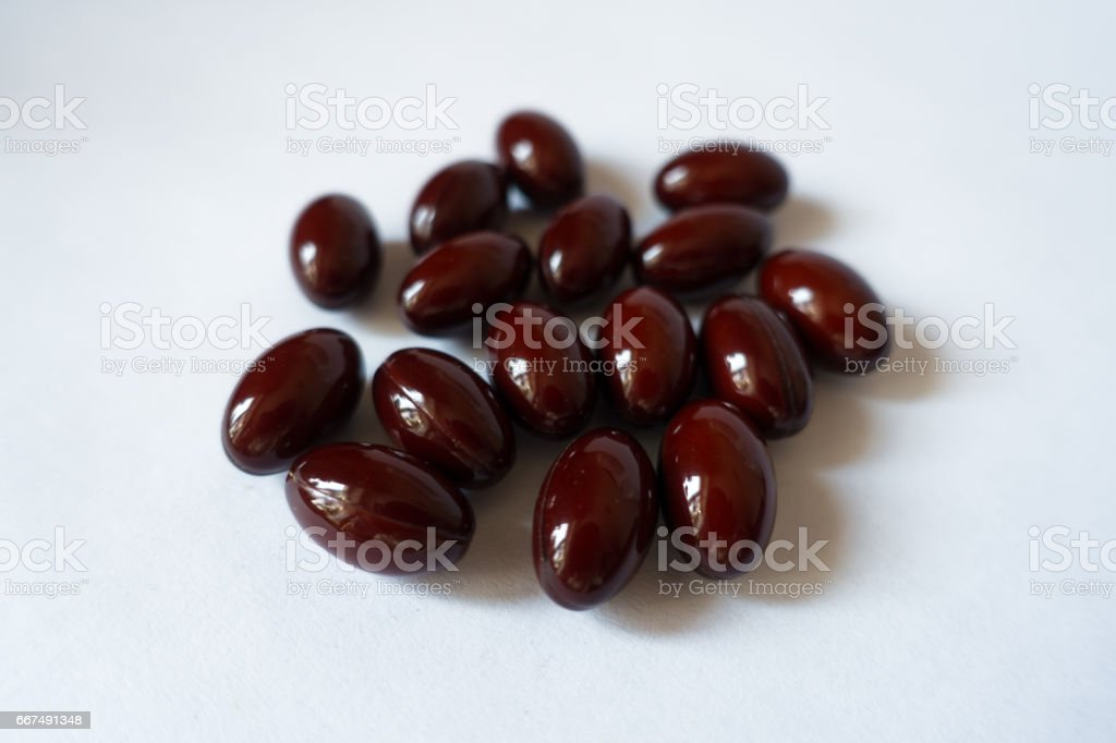 Close-up of handful of dark red lutein capsules on white background stock photo