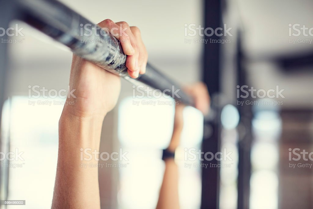 Close-up of hands holding pull-up bar in gym stock photo
