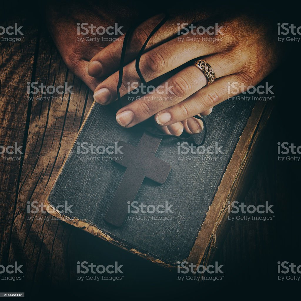closeup of hands holding vintage cross on Bible stock photo