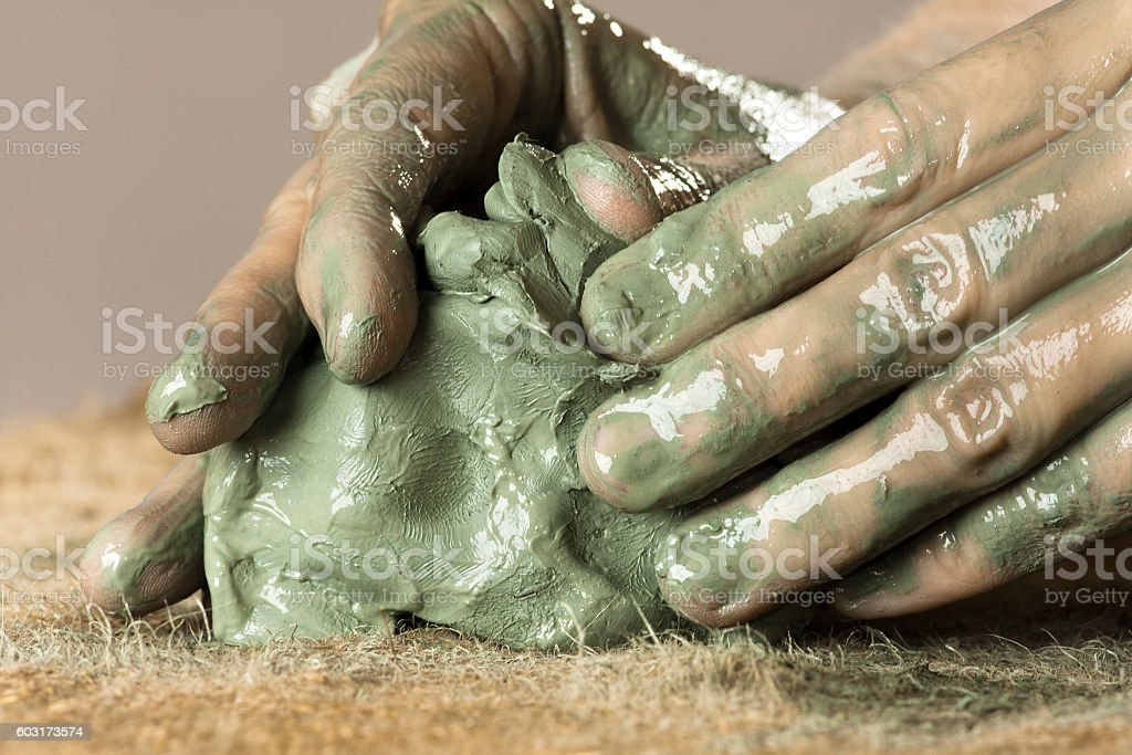 closeup of hands kneading blue clay stock photo