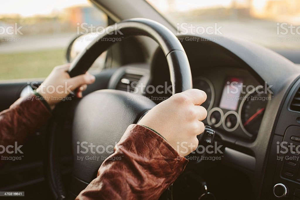 Close-up of hands on car steering wheel at 10 and 2 stock photo
