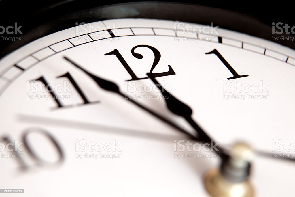 Closeup of hands on clock face stock photo