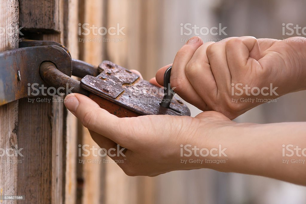 closeup of hands opening the padlock stock photo