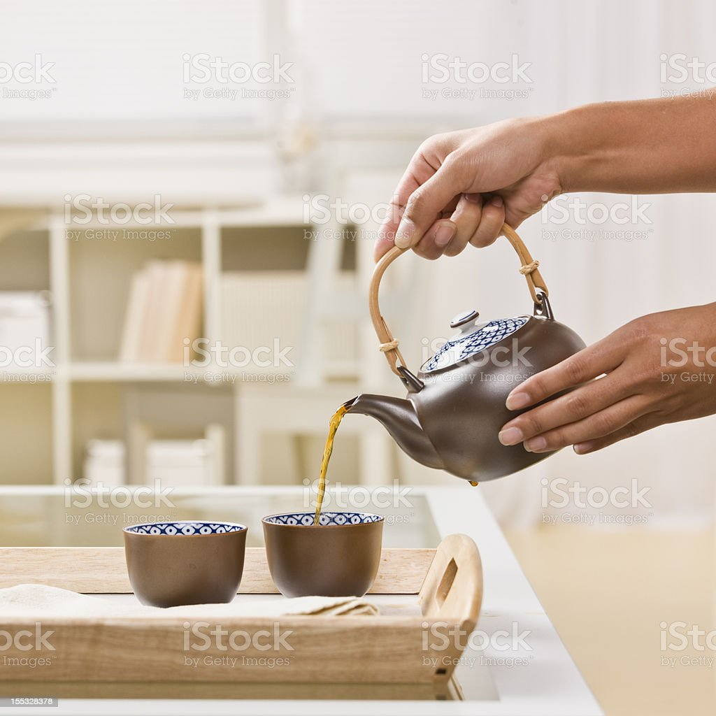 Close-up of Hands Pouring Tea royalty-free stock photo