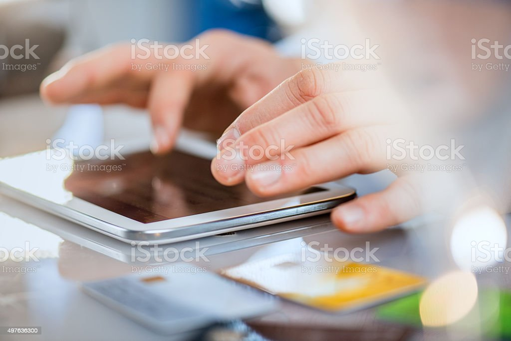 Close-up of hands typing on tablet and credit cards stock photo
