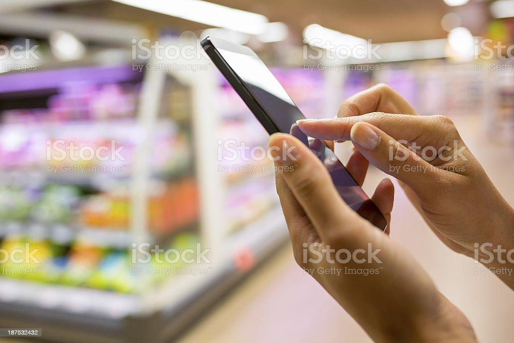 Closeup of hands using smartphone in supermarket stock photo