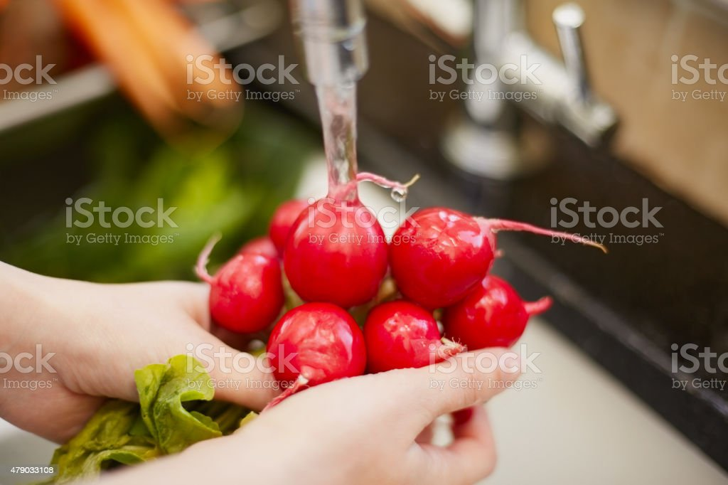 Close-up of hands washing red radishes stock photo