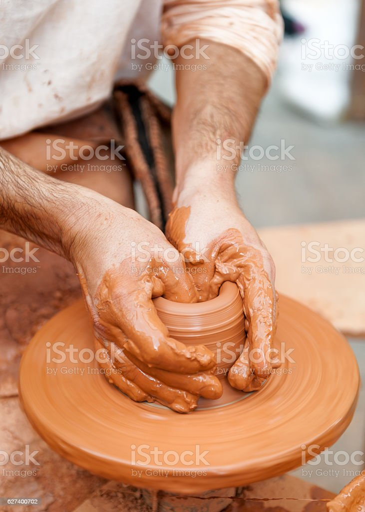 close-up of hands working with clay on turntable artisan stock photo