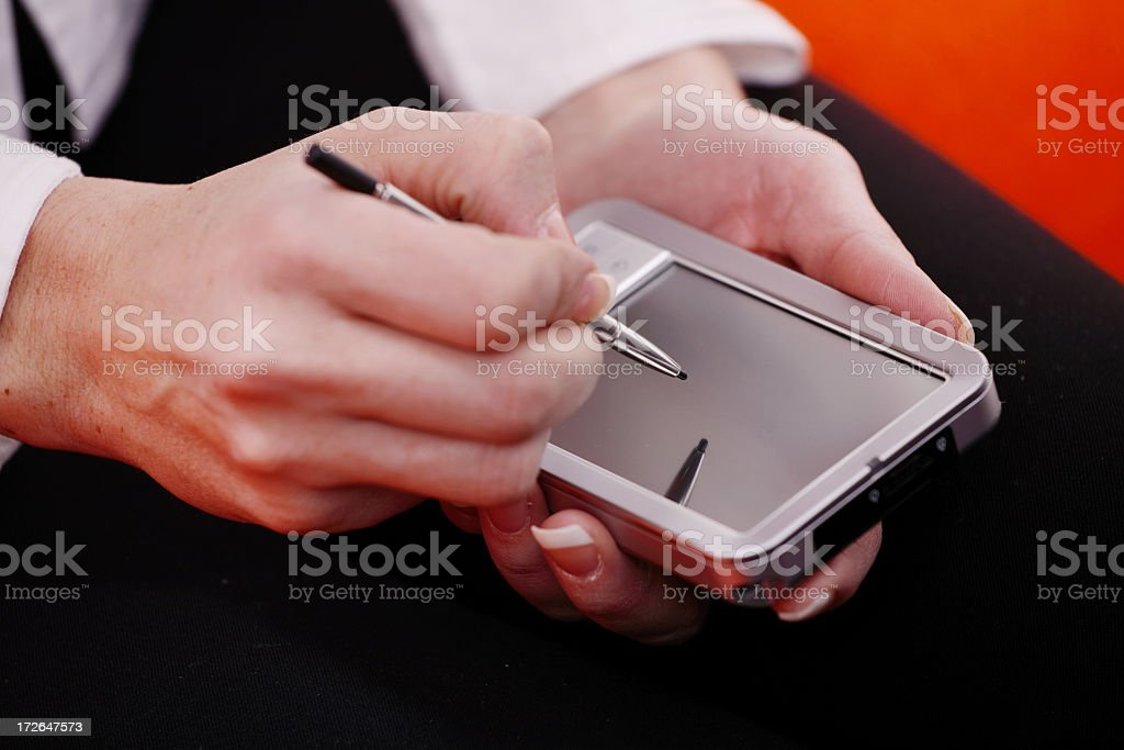 Close-up of hands writing on PDA royalty-free stock photo