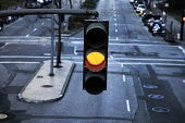 Close-up of hanging traffic light with yellow light on