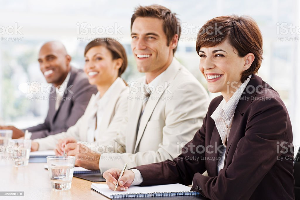 Closeup Of Happy Businesspeople At Boardroom Meeting stock photo
