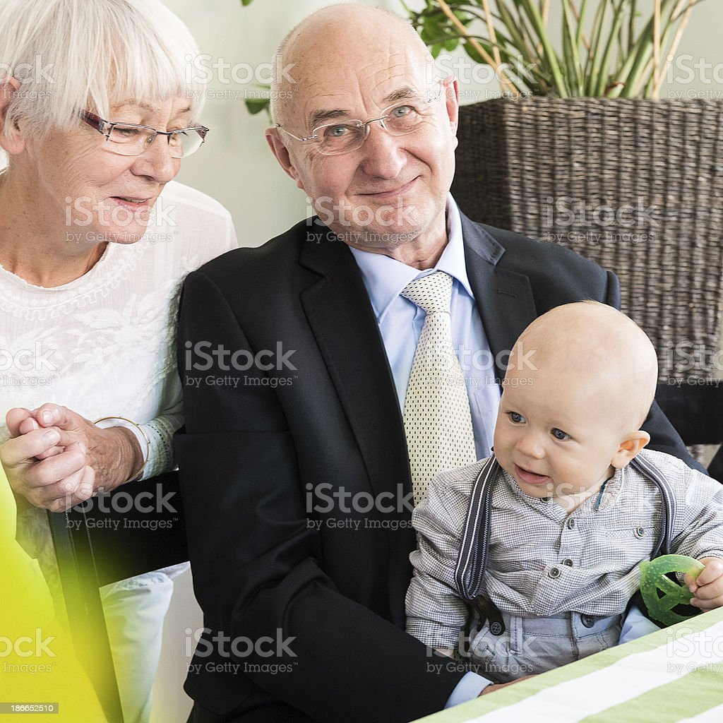 Close-up of happy grandparents with grandson in home interior royalty-free stock photo