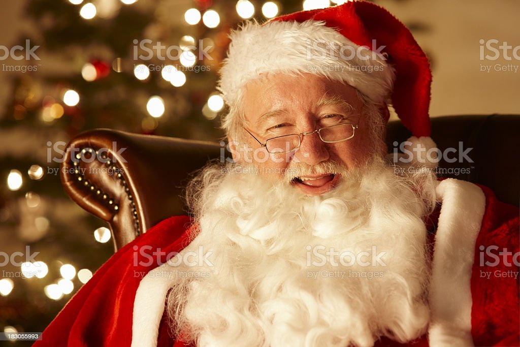 closeup of happy Santa relaxing by a Christmas tree royalty-free stock photo