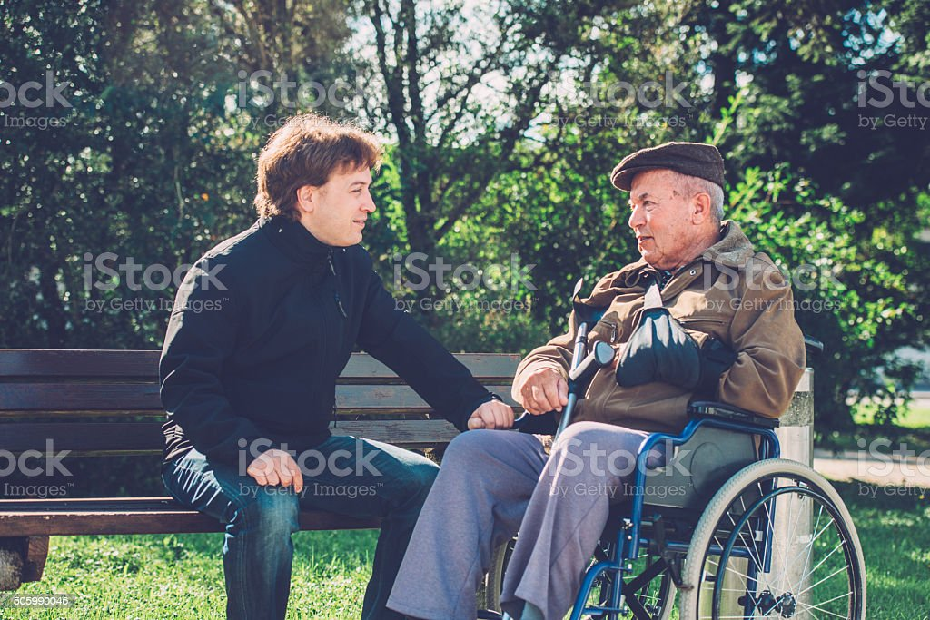 Close-Up of Happy Senior Man in Wheelchair and Grandson Outdoors stock photo