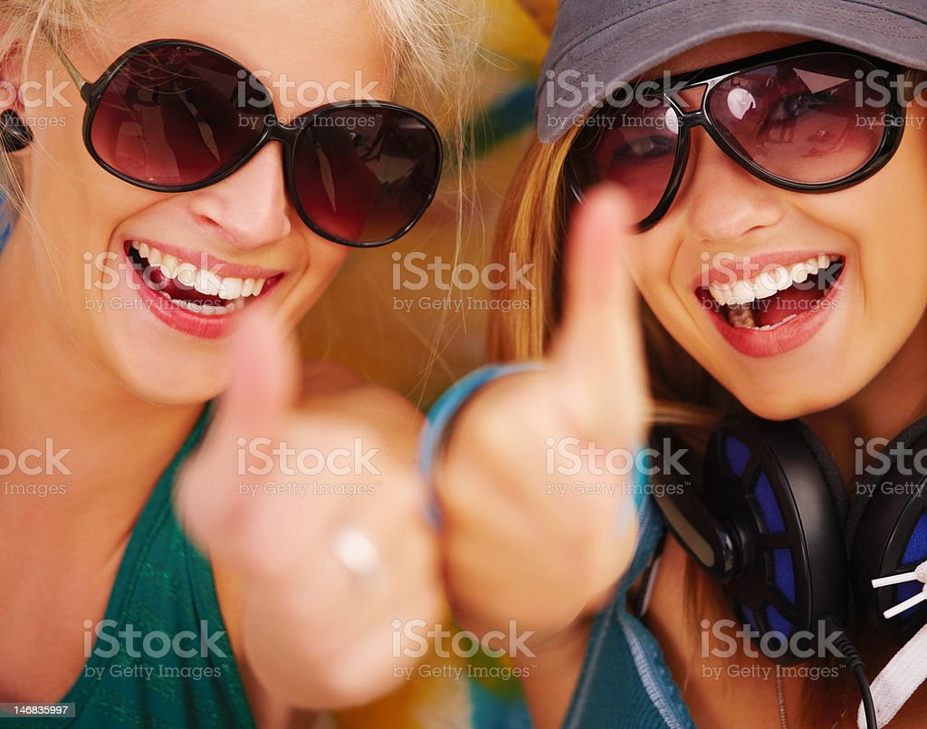 Close-up of happy teenage girls showing thumbs up sign royalty-free stock photo