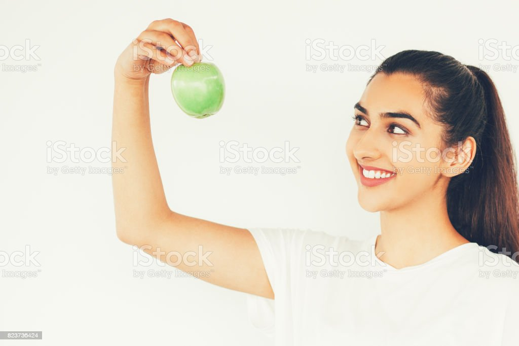 Closeup of Happy Young Indian Woman Raising Apple stock photo