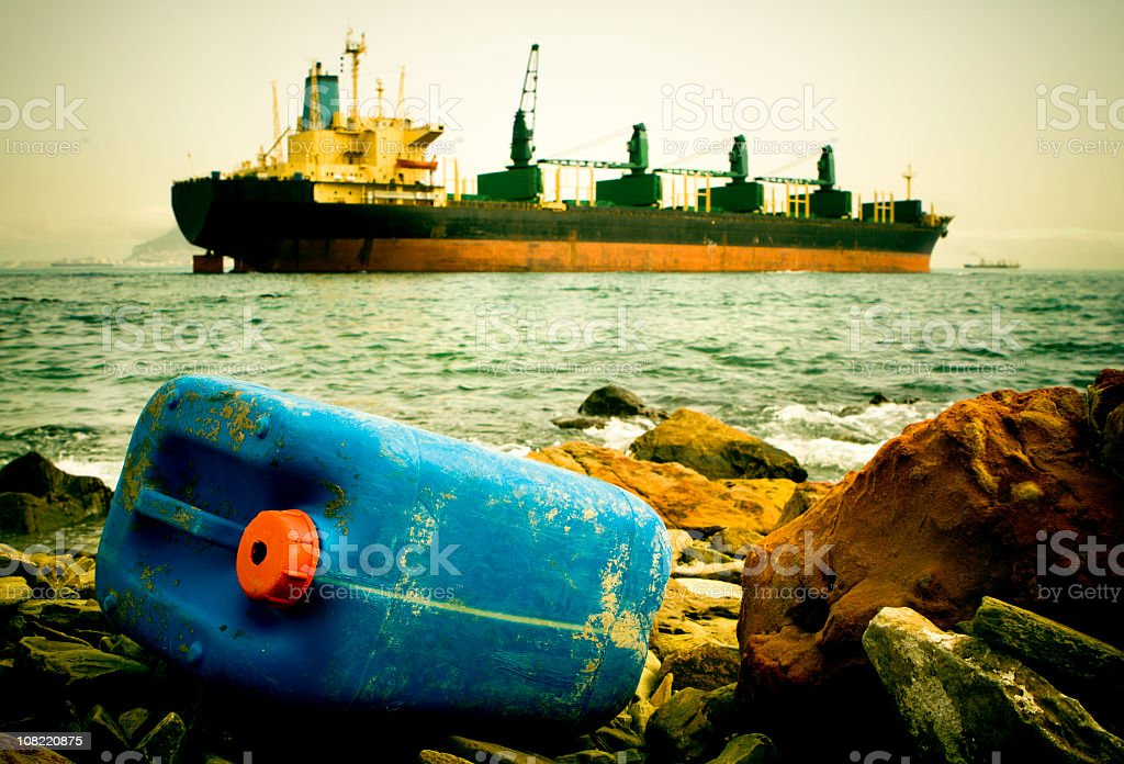 Close-up of hazardous waste with a boat in the background stock photo