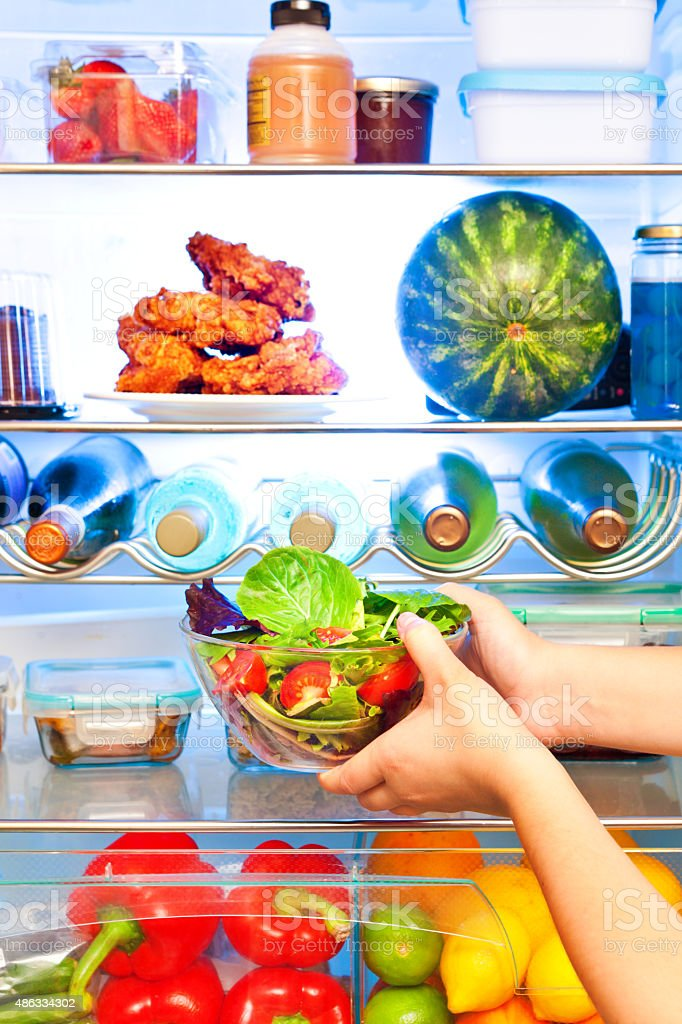 Close-up of Healthy Salad in Front of Open Refrigerator stock photo