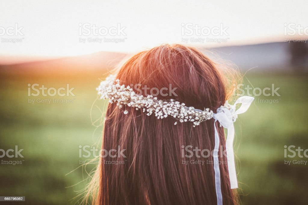 Close-up of hipster girl with a wreath in her hair on a sunny summer day stock photo