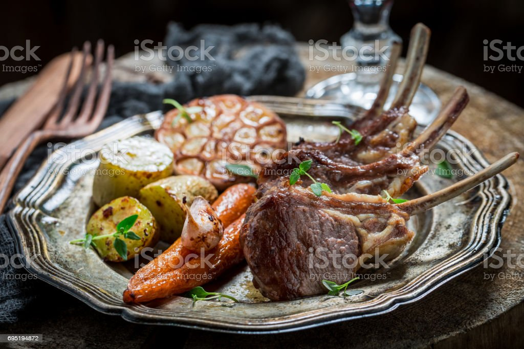 Closeup of hot roasted lamb ribs with garlic and vegetables stock photo