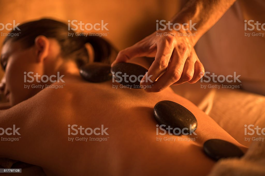 Close-up of hot stone therapy at the spa. stock photo