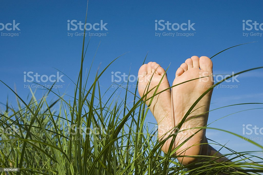 Close-up of human feet relaxing on grass under blue sky stock photo