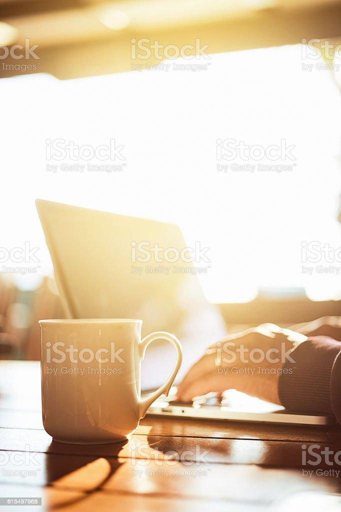 Close-up of human hand on laptop keyboard and coffee mug stock photo