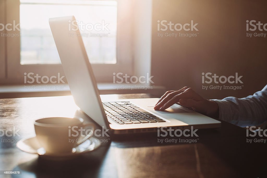 Close-up of human hand on laptop keyboard stock photo