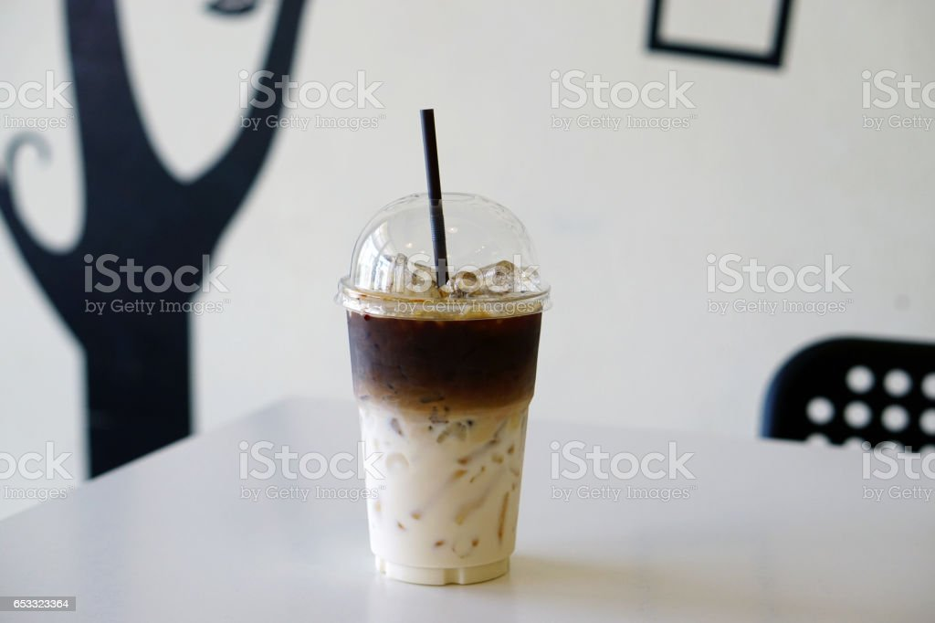 Closeup of Iced Caramel Macchiato at the coffee shop, Caramel Macchiato is a classic macchiato beverage. It consists of vanilla syrup, espresso, steamed milk, foam, and caramel drizzle. stock photo