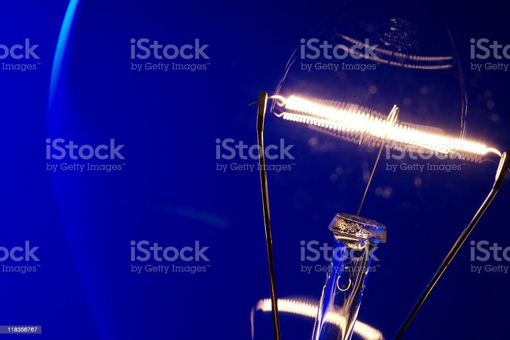 Close-up of illuminated light bulb against blue background stock photo