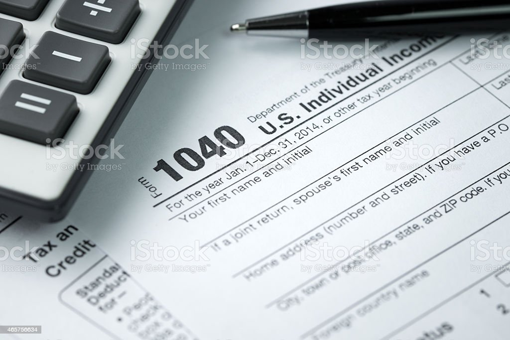 Closeup of income tax forms next to a calculator stock photo