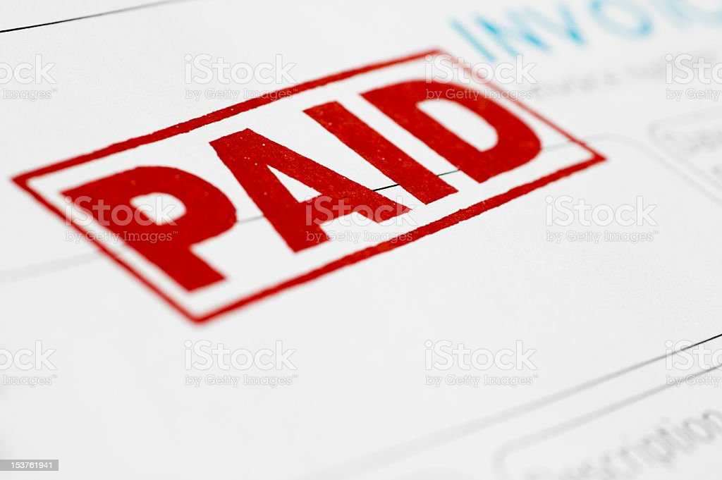 Close-up of invoice stamped as paid in red stock photo