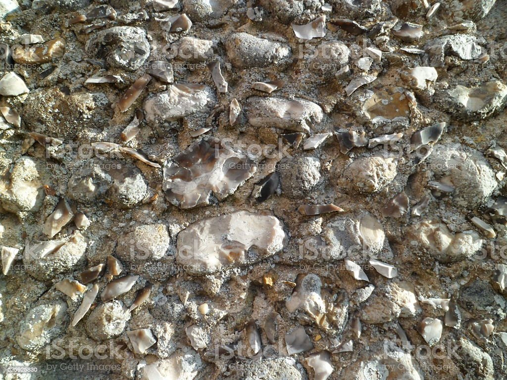 Close-up of irregular flint and mortar church wall stock photo