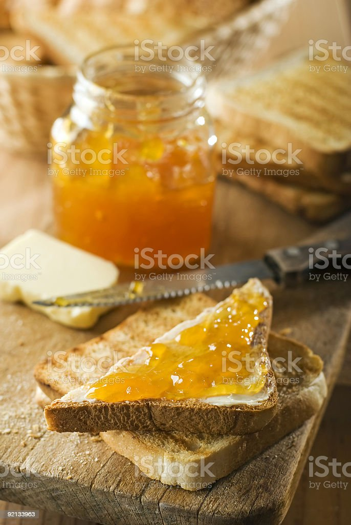 Close-up of jam on a piece of toast on a wooden table stock photo