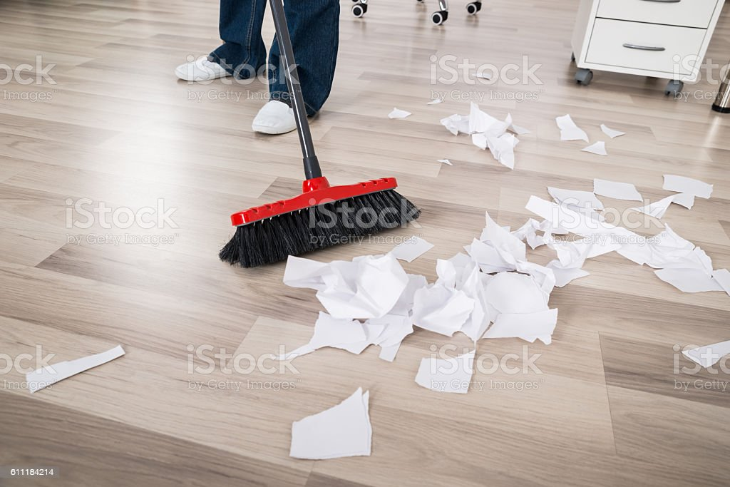 Close-up Of Janitor Sweeping Hardwood Floor stock photo