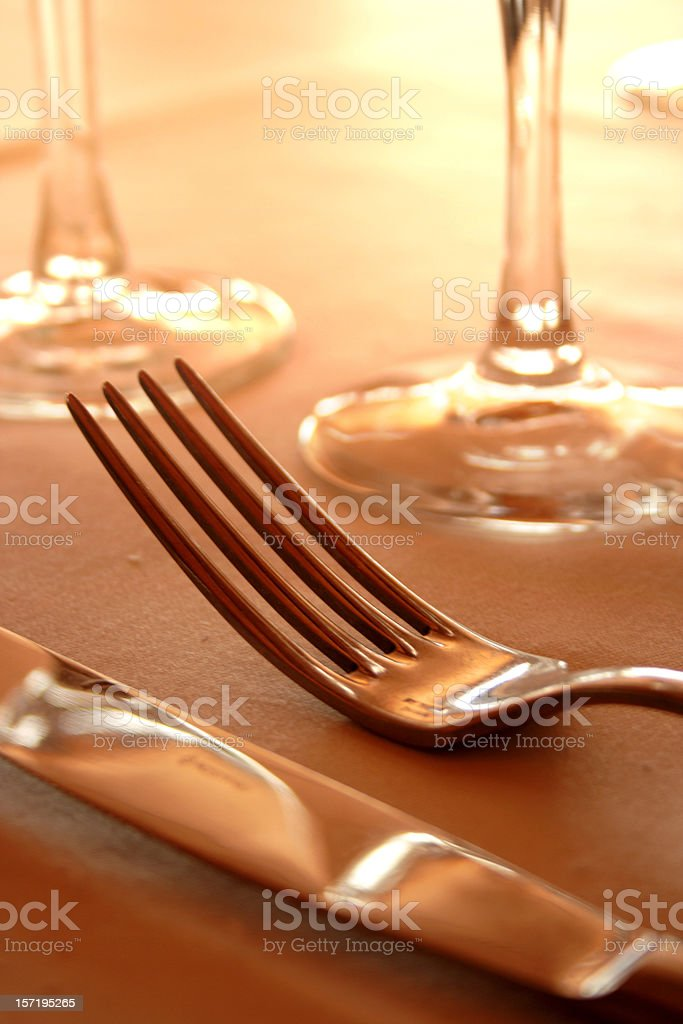 Close-up of knife and fork in front of wine glasses royalty-free stock photo