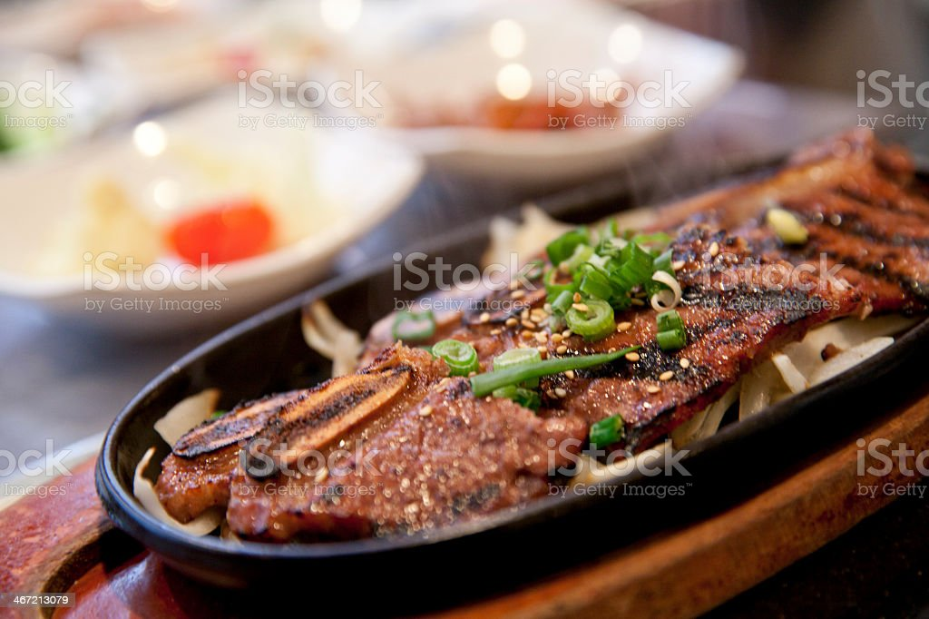 A close-up of Korean BBQ short ribs in a black dish stock photo
