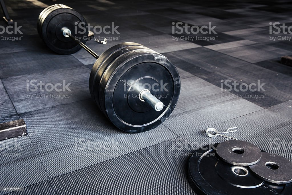 Closeup of large bar bell on gym floor stock photo