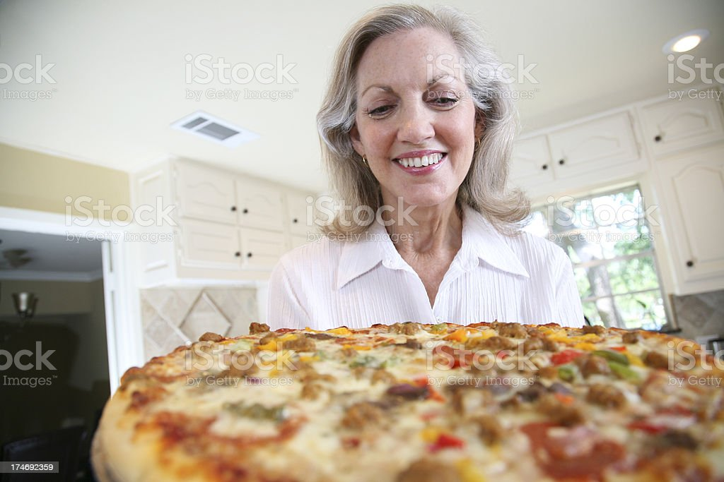 Closeup of Large Supreme Pizza Held By Smiling Senior Adult royalty-free stock photo